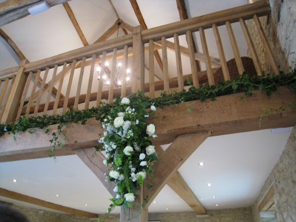 Floral decorations in cream and green set against the stone and wood  barn interior. Image by Tempting Cake