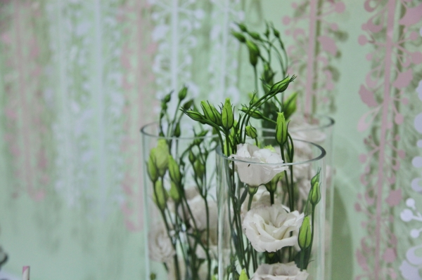 Lisianthus by Vanilla Rose peeking out of the top of a tall vase. Image by Charlotte Fielding